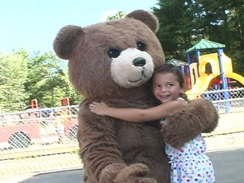 Girl hugging bear mascot
