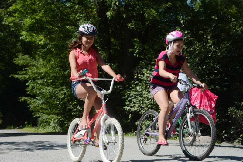 Two girls riding around the campground on their bikes