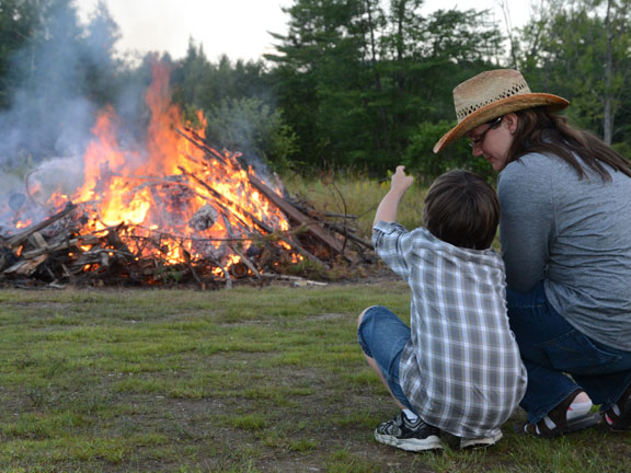Mother and son looking at a bonfire